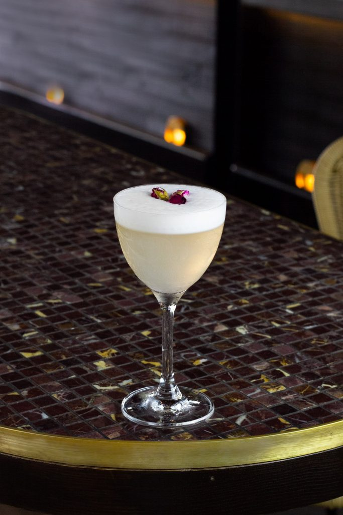 A frothy white cocktail with rosebud garnishes